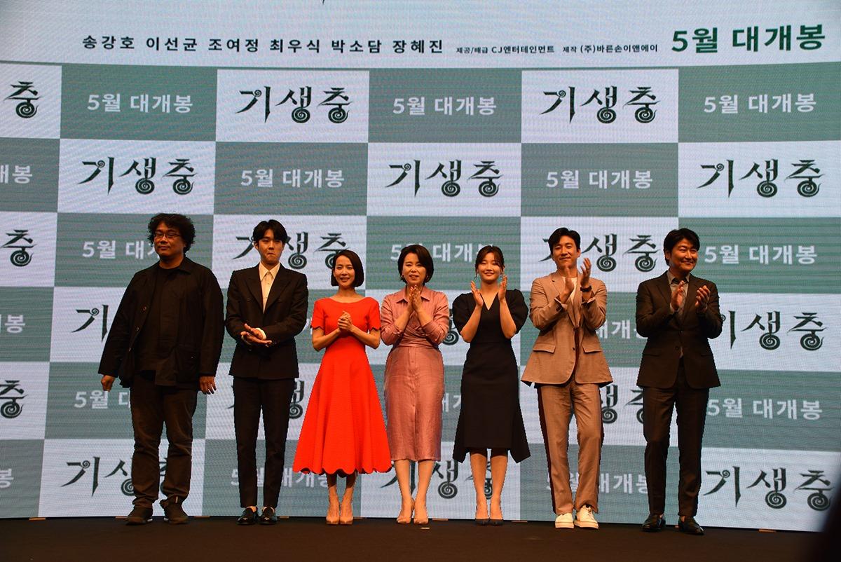 Photographie de l'équipe du film Parasite, avec 7 personnes dont tout à gauche le réalisateur Bong Joon Ho.