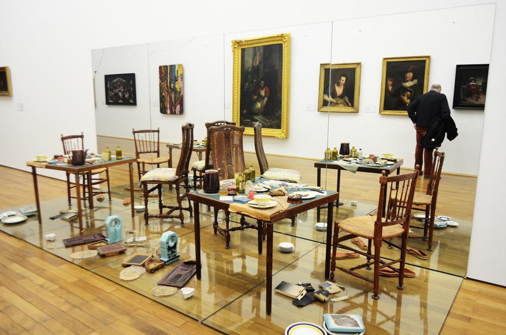 Photographie de l'installation de Daniel Spoerri en question, dressée au Musée d'Arts de Nantes et composée de tables, de chaises, d'assiettes sales, de couverts et de produits alimentaires d'une autre époque.