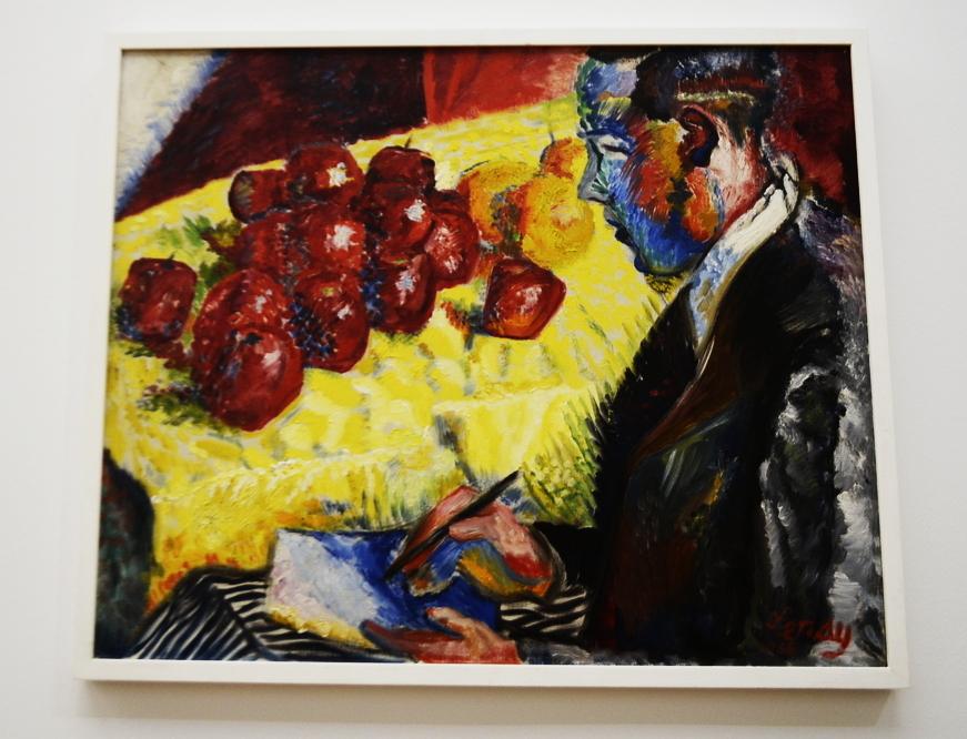 Photographie du tableau Légumes et fruits de Louis Valtat lors de son exposition au Musée d'art de Nantes. Il représente au premier plan un homme de profile écrivant sur un papier avec un stylo. En arrière-plan, des pommes rouges et des oranges sont posés sur un tissu jaune, étendu sur un canapé.