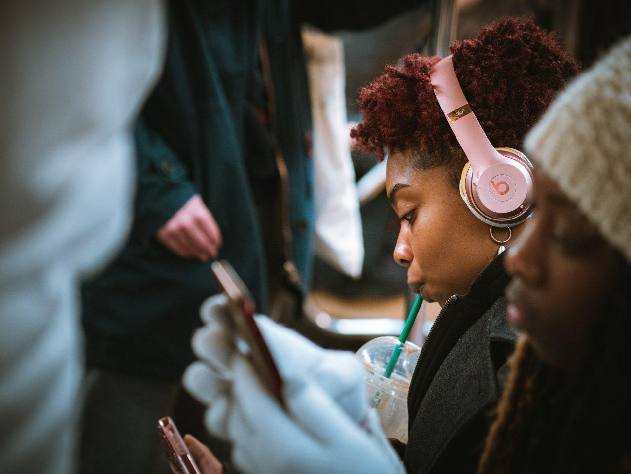 Une femme est assise dans les transports en commun et écoute avec un casque un livre audio tout en consultant son téléphone.