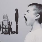 Image en noir et blanc montrant au premier plan un enfant qui semble crier dans un micro d'enregistrement (tel que ceux qu'on utilise pour enregistrer des morceaux de musique ou des livres audio dans des studios). L'enfant est de profil sur la droite de la photo ; le micro à gauche.