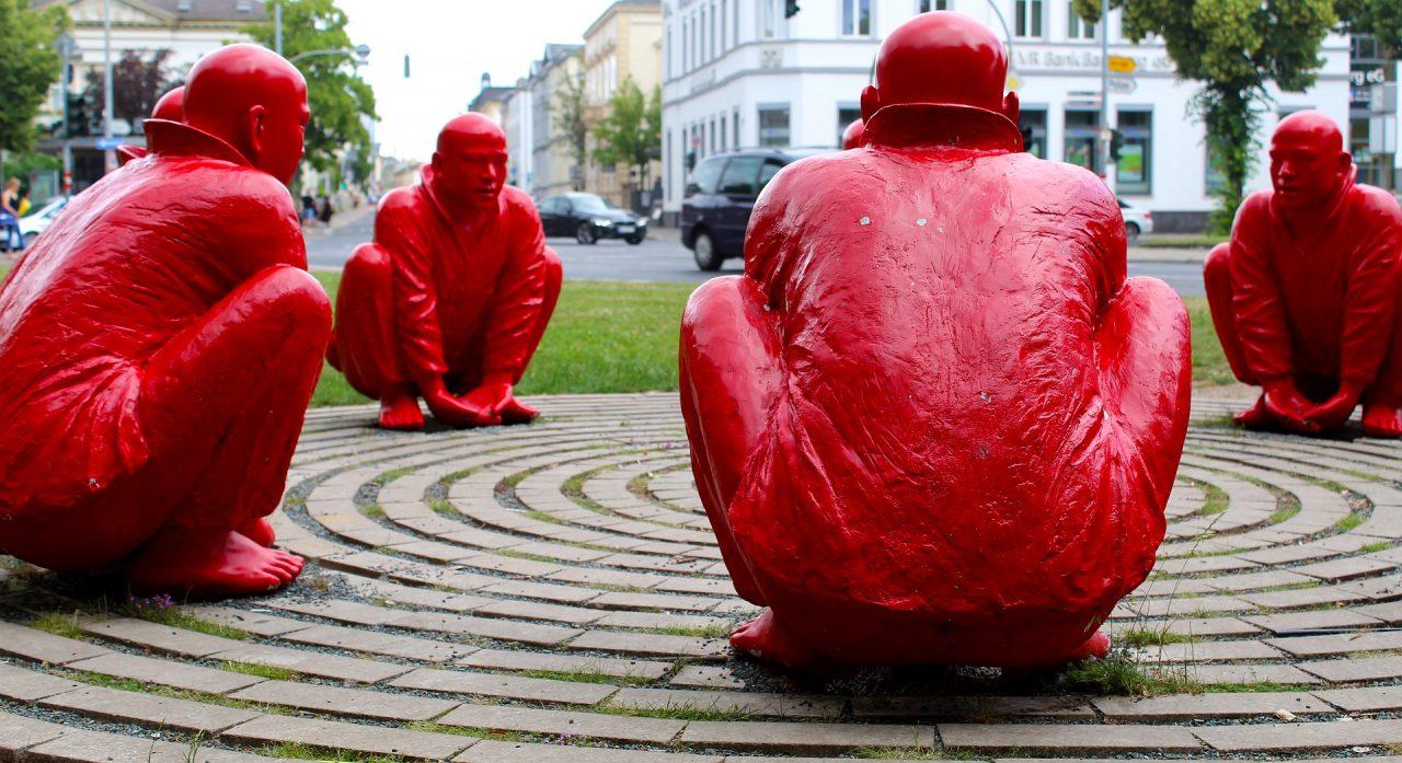 Photographie libre de droit montrant quatre statues d'homme chauves peints en rouge accroupis au quatre coins d'une spirale géante.