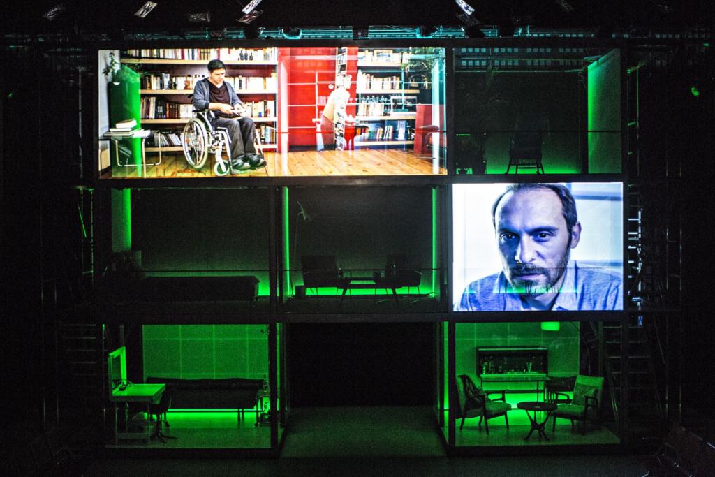 Photo de la mise en scène de la pièce jouée au Grand T. Des échafaudages ont été installés et formes un carré subdivisé en neuf carrés plus petits. La scène est éclairée d'une lumière verte. Trois des cases montrent des projections de vidéos sur lesquelles on voit des hommes.