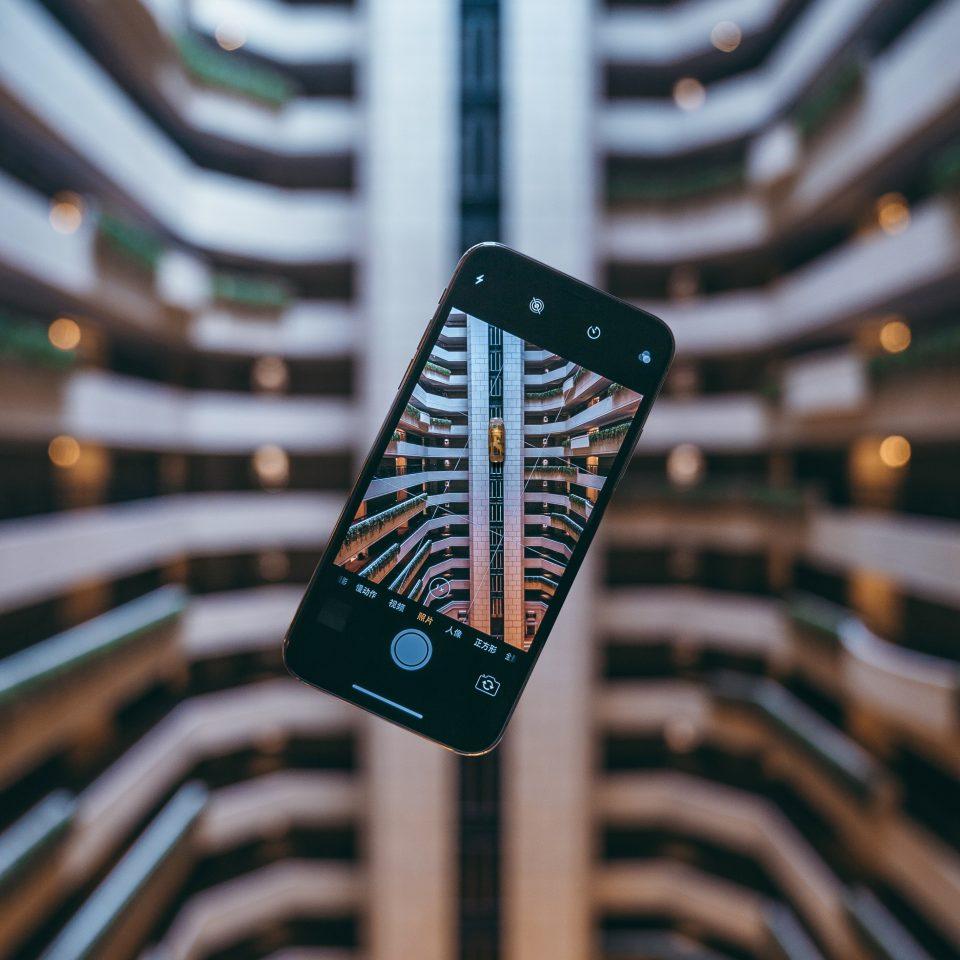 """Photographie illustrant le principe d'une exposition virtuelle. Sur le fonds, une pièce d'architecture : un escalier ou des étages. Au premier plan, un smartphone en mode """"photographie""""."""