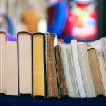 Photographie montrant une rangée de livres en zoom sur une étagère. On ne voit pas les tranches des ouvrages (et donc pas leurs titres) mais leurs pages. L'effet de la photo est très coloré et lumineux.