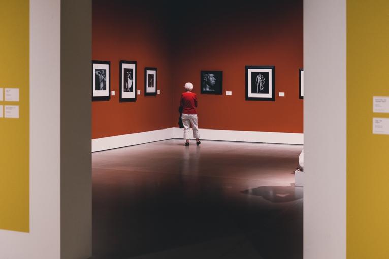 Photographie prise dans un musée. On y voit une personne seule au milieu d'une salle d'exposition aux murs rouges. Des oeuvres entourées de cadres blancs sont exposées.