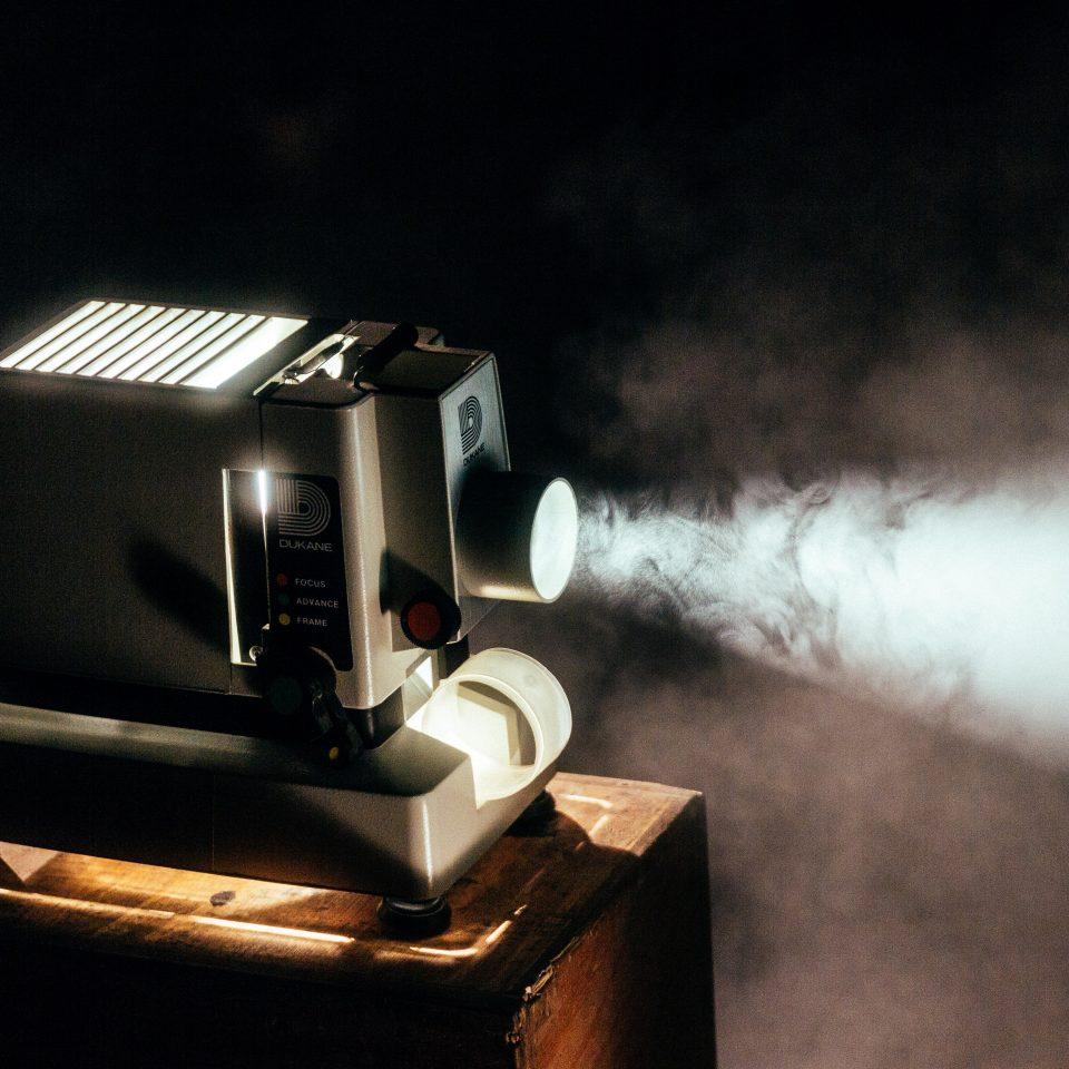 Photographie d'un projecteur en fonctionnement, pour illustrer le top 10 des films à visionner pendant le confinement. La machine, grise, est posée sur un tabouret en bois dans une pièce plongée dans l'obscurité. Un faisceau blanc sort du projecteur, projetant les images (que l'on ne voit pas dans le cadre de la photographie).