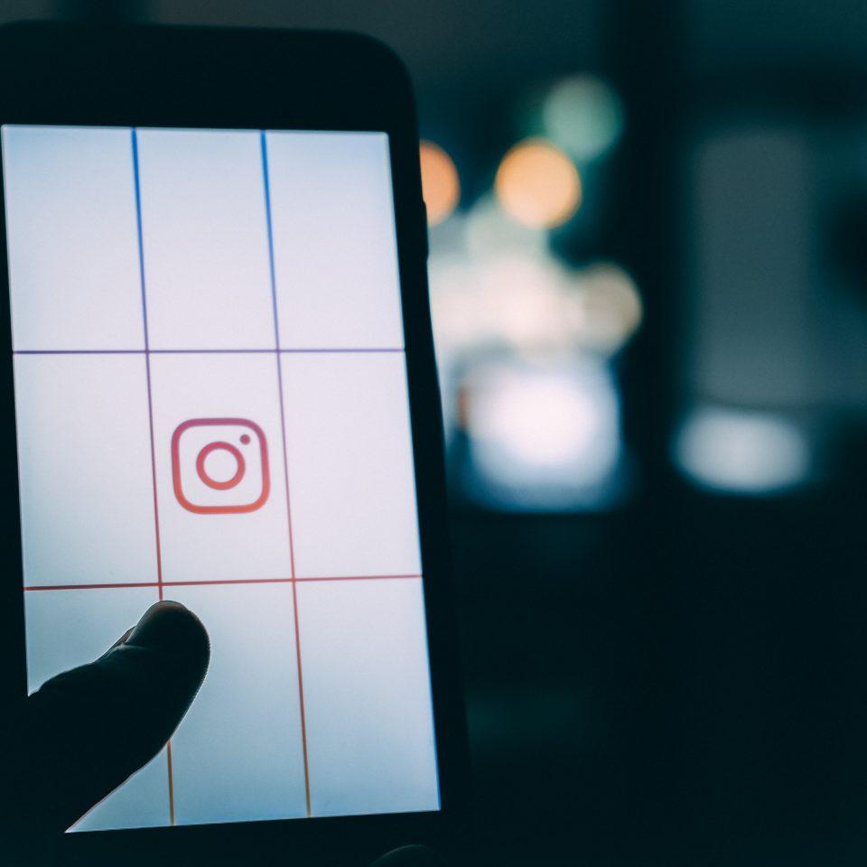 Photographie prise dans le noir d'un téléphone lumineux ouvert sur le logiciel Instagram.