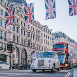 Photographie d'une rue dans la ville de Londres. Un taxi anglais et un bus à impériale roulent sous des bannières adorant le drapeau du Royaume-Uni.