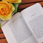Un livre est ouvert sur une table en bois. C'est le début d'un chapitre. Une fleur jaune orangée est visible de haut dans le coin supérieur gauche.