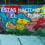 """Photographie illustrant le thème """"cultural industries"""". Mur coloré, peint avec une oeuvre de street art. Une écriture transparaît en blanc: que faites-vous pour changer le monde (sur la photo, en espagnol) ?"""
