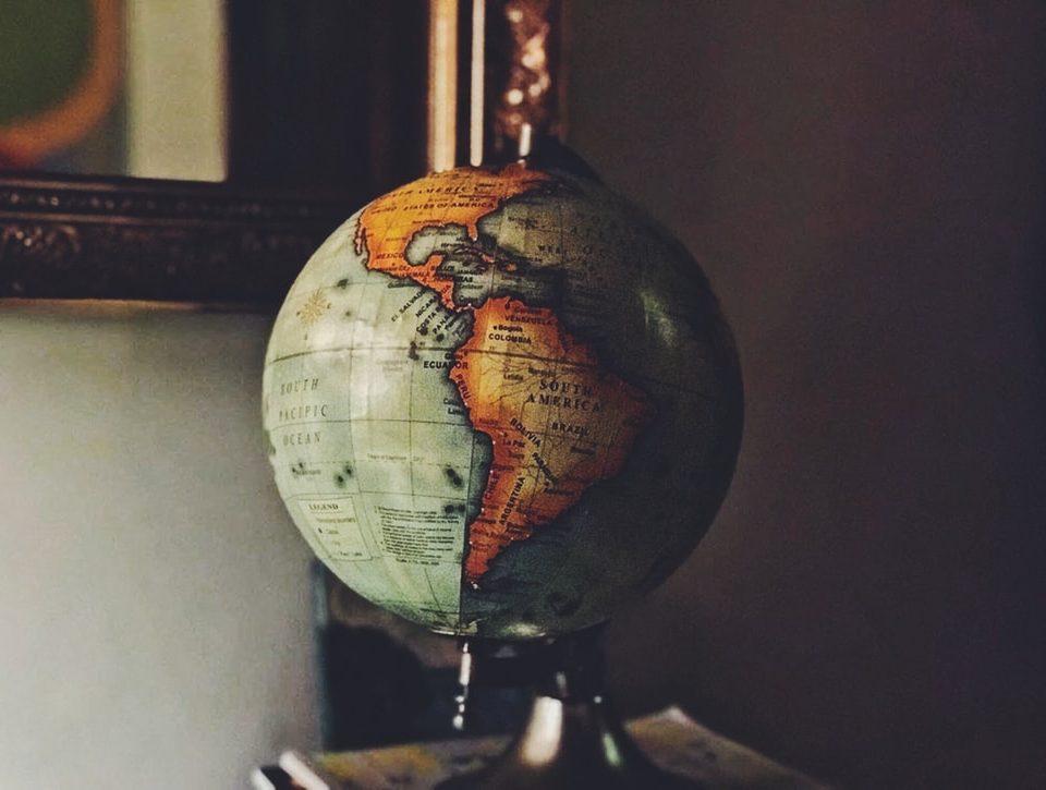 """Photographie avec un filtre old school. Un globe terrestre est posé sur une étagère et représente le """"tour du monde des initiatives culturelles durant le confinement"""" proposé dans l'article."""