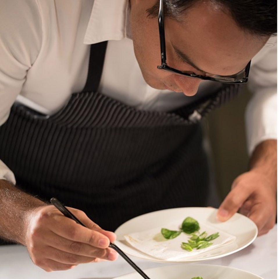 Photo de Guillermo Muro capturant un cuisiner en train de décorer méticuleusement un plat.